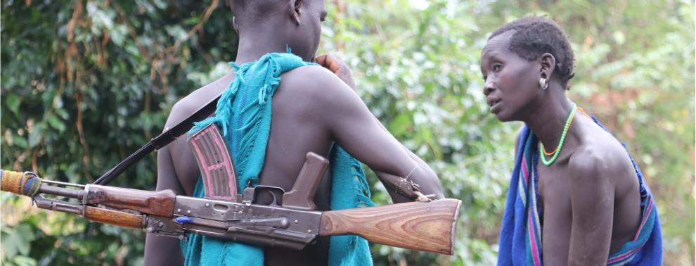 Befremdliche Szene: Jugendlicher Stammesjunge mit AK 47 inmitten scheinbar unberührter Zivilisation.